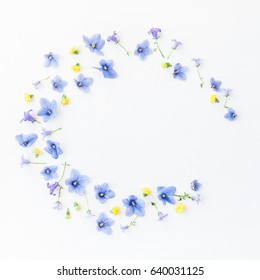 Wreath made of bell flowers, pansy flowers and yellow flowers on white background. Flat lay, top view