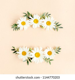 Wreath made of chamomiles, petals, leaves on beige background. Flat lay, top view floral background.