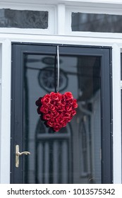 A wreath made out of red roses hanging on the front door awaiting for love and spreading kindness to all walkers