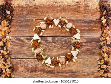 Wreath made of spices. Star anise, nutmeg, green cardamom, hearts made of sugar, border of sugar and cloves on wooden background. Top view.