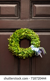 Wreath made of tiny green leaves hanging on a wood paneled front door. Close up