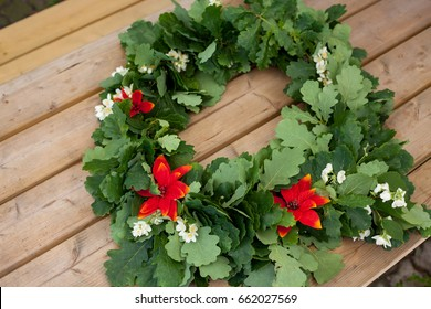 Wreath from oak leaves with jasmine and red flowers on wooden background. Midsummer in Latvia. Celebration of Ligo feast in June
