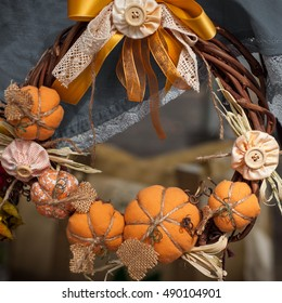 Wreath on the door decorated with textile pumpkins