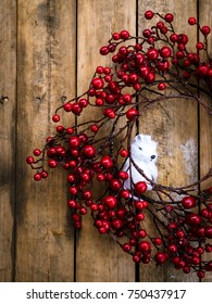 Wreath of red berries with a small white mouse on rustic wooden door