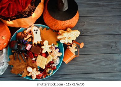 a wreath of red roses on the head of a Halloween pumpkin  with Halloween Jack o Lantern candy bowl