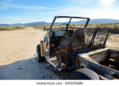 Wreck of an ancient pick-up, completely destroyed, abandoned in the desert.