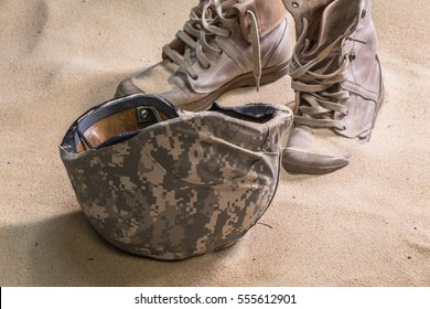 Wreck bulletproof helmet Military boots and goggles sand in the desert It sank in the sand