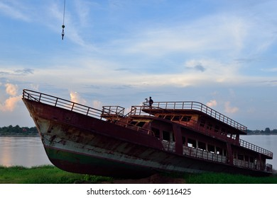 Wreck of a large boat landing on the Mekong River in the evening, Thailand.