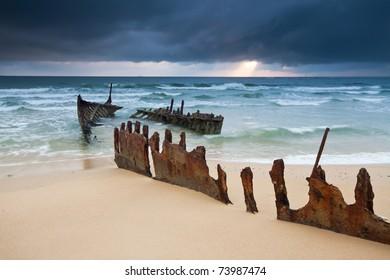 wreck on australian beach at sunrise (ss dicky wreck,dicky beach, queensland)