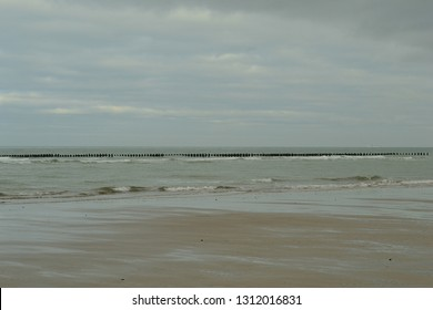 wreck of wooden boat in the water and woosen piles in the water for bouchot in the north of France, Tattinghen beach, Opal Coast, Pas de Calais