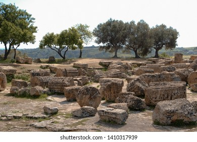 A lot of wreckage brick and stone from Greek valley of the temples in Agrigento, Sicily all over the place in the middle of the field in the moutain with the clear sky