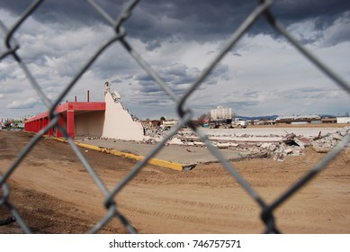 The wreckage of an in-progress demolition big box retail store behind a blurred chainlink fence.  Rebar protrudes from the walls