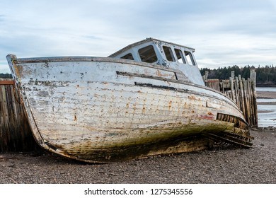 A wrecked boat on the shore next to a dilapidated wharf. Both the boat and wharf are in very poor shape and are falling apart. Closeup view. Low tide.
