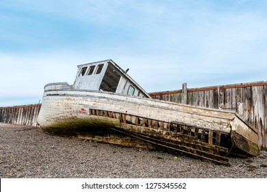A wrecked boat on the shore next to an old wharf. The boat is in very poor shape and is falling apart. Low tide.