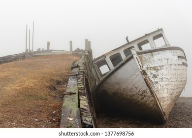 A wrecked boat on the shore next to an old abandoned wharf on a very foggy day. The boat is in very poor shape and is falling apart. Front view at low tide.