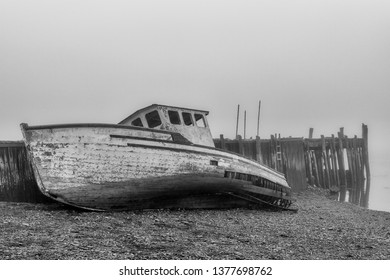 A wrecked boat on the shore next to an old abandoned wharf on a very foggy day. The boat is in very poor shape and is falling apart. Side view at low tide. Black and white.