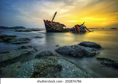 wrecked boat on a silent sea in sunset and golden twilight sky