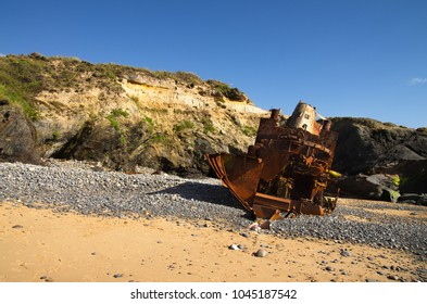 Wrecked, broken and destroyed old towboat at an cliff isolated beach near Vila Nova de Milfontes. Stern view. Portugal.