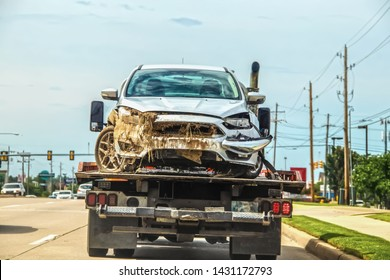 Wrecked car with mud and plant material sticking out of grill and from under hood on flatbed truck in city - possible in flood - selective focus