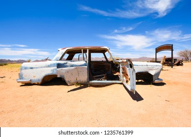 Wrecked cars lie abandoned in the desert surrounding Solitaire in Namibia.