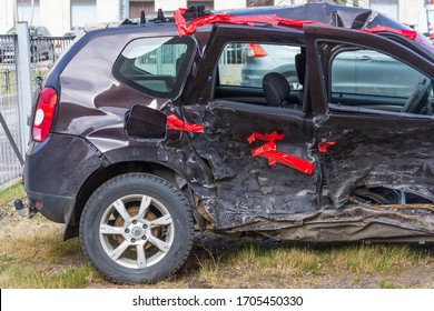 Wrecked crumpled car from the right side after a severe accident with a distorted body and broken windows, after a powerful impact side back view