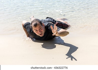 Wrecked man on the coastline stretches out his hand for help. Exhausted swimmer crawling on the beach from the sea. Castaway crawling from the sea.