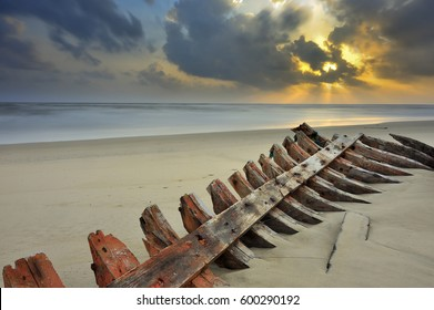 Wrecked ship on the beach with golden sunset background.soft focus effect  long exposure photography