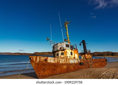 A wrecked ship on a sandy beach at low tide in the Teriberskaya Bay. Far North, Barents Sea in Russia.