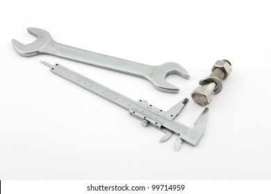 A wrench, a caliper and a screw with a nut are pictured on a white background.