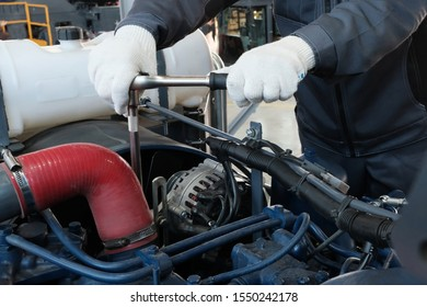 A wrench in male hands in white gloves. Close-up. Service center or industrial concept. A worker in a machine service factory tightens a bolt or nut. Car engine or tractor repair.