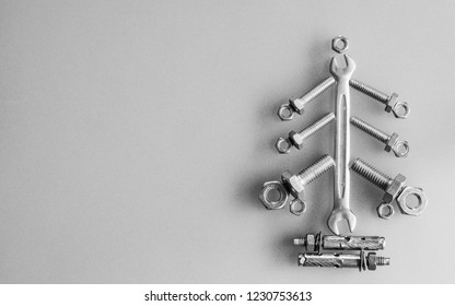 Wrench, nuts and bolts decorated as Christmas tree on a gray background. Christmas greeting card and Happy new year greeting card concept. Top view with copy space for your text