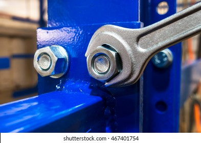 Wrench is tightening the chrome  nut on the blue metal folding shelf