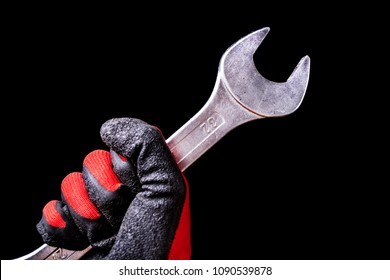 Wrench tool in hand with protective gloves isolated on black background. Close up