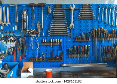 Wrenches set in the workshop. Some wrenchs and tools on the tool shelf. Work tools on the garage wall and work table. Workshop tool holder with a wrench and set of wrench sockets