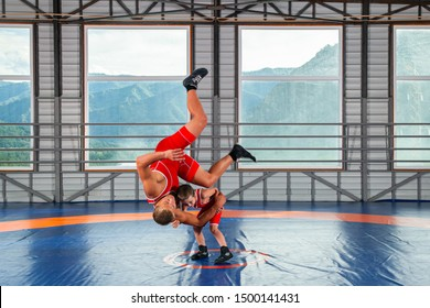 A  wrestler boy in a sports tights wrestles with an adult male wrestler on a wrestling carpet in the gym. The concept of child power and martial arts training. Teaching children Greco-Roman wrestling