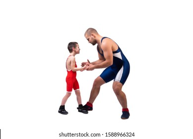 A  wrestler boy in a sports tights wrestles with an adult male wrestler on a white isolated background. The concept of child power and martial arts training. Teaching children Greco-Roman wrestling
