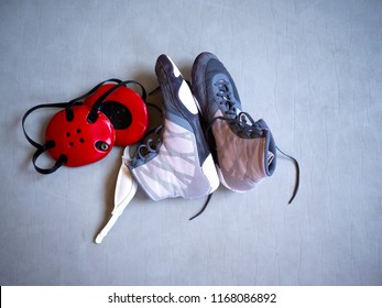 Wrestling shoes and headgear on a grey mat