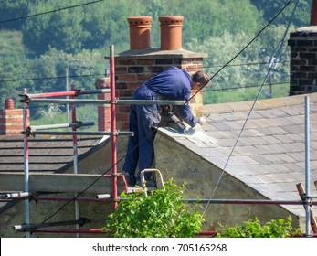 Construction worker pointing up stock photos images photography wrexham uk may 25 2017 roofer repairing flashing on chimney stack on malvernweather Images