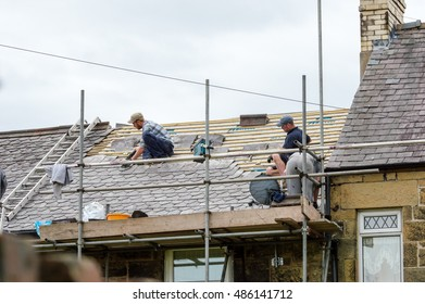 WREXHAM, WALES, UNITED KINGDOM - AUGUST 10, 2016: Restoration of decorative slate roof on a residential terraced house in North Wales. With three workmen.