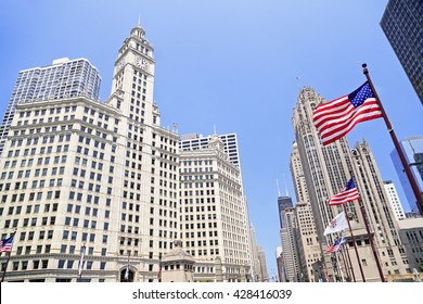 Wrigley Building and Tribune Tower on Michigan Avenue with American flag on the foreground in Chicago, USA