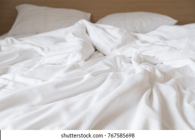 wrinkle messy blanket in bedroom after waking up in the morning, from sleeping in a long night, details of duvet and blanket, an unmade bed in hotel bedroom with white blanket.