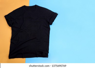 Wrinkled black mockup t-shirt on orange and blue pastel background