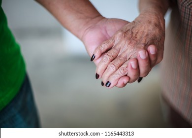 wrinkled elderly woman's hand holding to young man's hand, walking in shopping mall park. Family Relation, Health, Help, Support, Insurance concept.