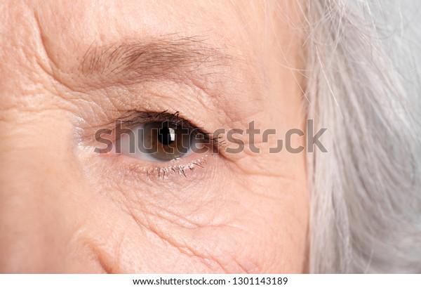 Wrinkled face of elderly woman, closeup of eye
