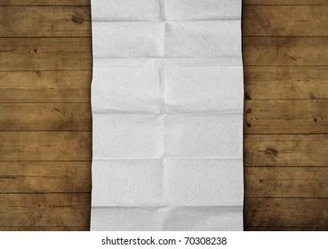 wrinkled fold paper on old wooden background