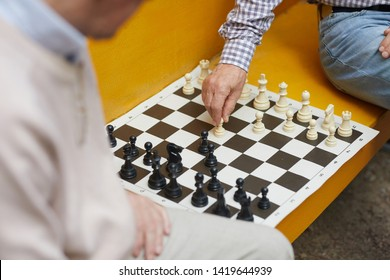 Wrinkled hand of old chess player moving white figure during playing chess on yellow bench