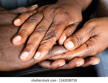 Wrinkled Hands of an elderly black woman holding the hand of a young African American man.  Old and young holding hands on dark background, closeup for retirement, support and Care concept