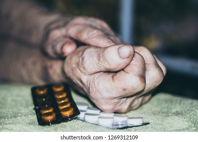 Wrinkled hands of old sick woman and pills