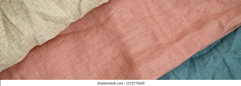 Wrinkled linen cloth folded napkins. Linen fabric texture. Stone washed petrol blue, rose, pure linen background