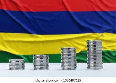 Wrinkled Mauritius flag in the background with rows of coins for finance and business concept. Saving money.